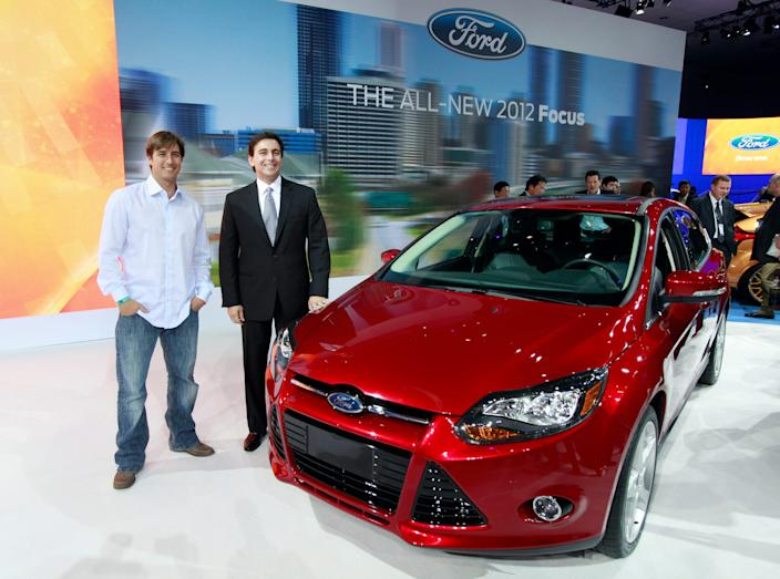 Mark Fields, Ford president for the Americas, right, and Olympic skier Johnny Moseley pose with the 2012 model year Ford Focus makes its debut at the LA Auto Show Wednesday, Nov. 17, 2010. Moseley is scheduled to host a reality-type TV show titled