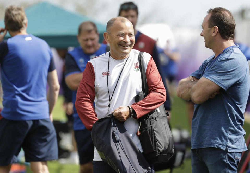 England rugby coach Eddie Jones, center, smiles as he talks during training at Beppu, Japan, Tuesday Oct. 15, 2019. England will play Australia in the quarterfinals of the Rugby World Cup on Oct. 19. (AP Photo/Aaron Favila)