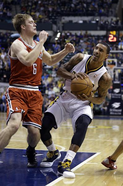 Indiana Pacers guard George Hill, right, cuts under Milwaukee Bucks guard Nate Wolters in the second half of an NBA basketball game in Indianapolis, Friday, Nov. 15, 2013. The Pacers defeated the Bucks 104-77. (AP Photo/Michael Conroy)