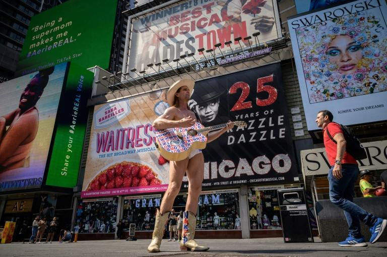 The Naked Cowboy stands before billboards advertising broadway musicals, on Times Square in New York on September 14, 2021 (AFP/Ed JONES)