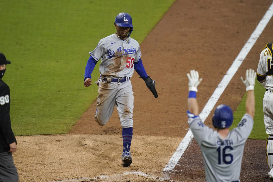 Los Angeles Dodgers' Mookie Betts scores on a single by Justin Turner during the ninth inning of the team's baseball game against the San Diego Padres, Friday, April 16, 2021, in San Diego. (AP Photo/Gregory Bull)