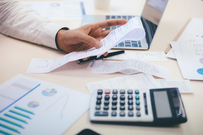 Cropped Image Of Hand Holding Financial Bill With Graph And Laptop On Table