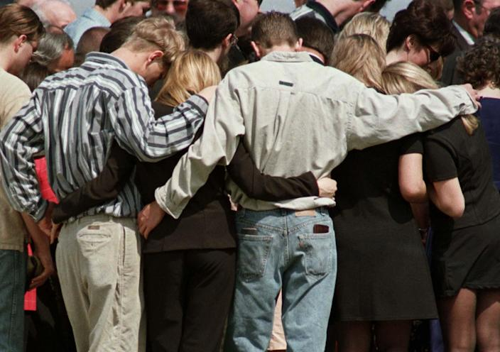 Students of Westside School bow their heads in prayer at the burial service for teacher Shannon Wright, March 28, 1998. Wright was killed while using her body to shield students from gunfire. (Photo: John Kuntz/Reuters)