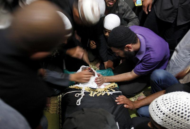Palestinian mourners gather around the body of Salafi militant Hisham Saidani during his funeral in Bureij refugee camp, central Gaza Strip, Sunday, Oct. 14, 2012. Saidani, a member of a faction of the ultraconservative Salafi trend believed to have ties to al-Qaida, was one of two people killed in an Israeli airstrike on Saturday. Saidani is suspected of carrying out attacks against Israeli and Egyptian targets. (AP Photo/ Hatem Moussa)