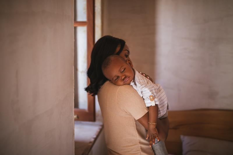 Young mother affectionately embracing and holding little sleeping son in her arms