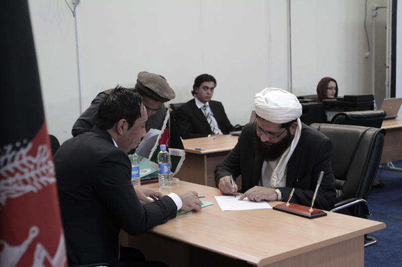 Former head of the Hezb-e-Islami delegation, Qudbuddin Helal, right, registers his candidacy in next year's presidential election at the independent election commission office in Kabul, Afghanistan, Saturday, Oct. 5, 2013. (AP Photo/Rahmat Gul)