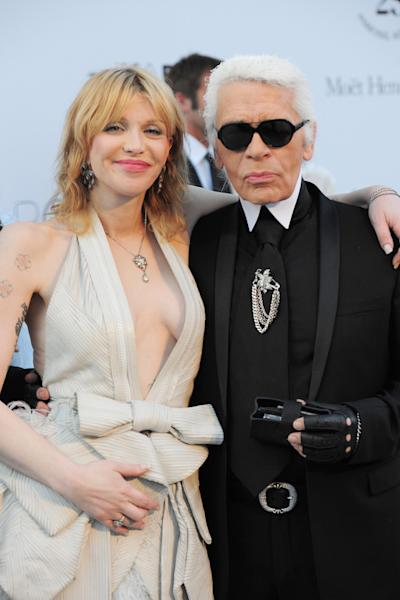 US musician Courtney Love and German fashion designer Karl Lagerfeld posing upon arrival to the 2011 amfAR's Cinema Against Aids benefit gala on the sidelines of the 64th Cannes Film Festival on May 19, 2011 in Antibes