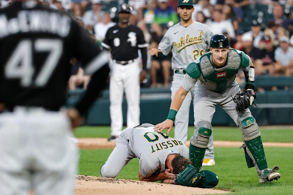 Oakland Athletics catcher Sean Murphy checks on starter Chris Bassitt after the pitcher was hit in the head by a line drive.