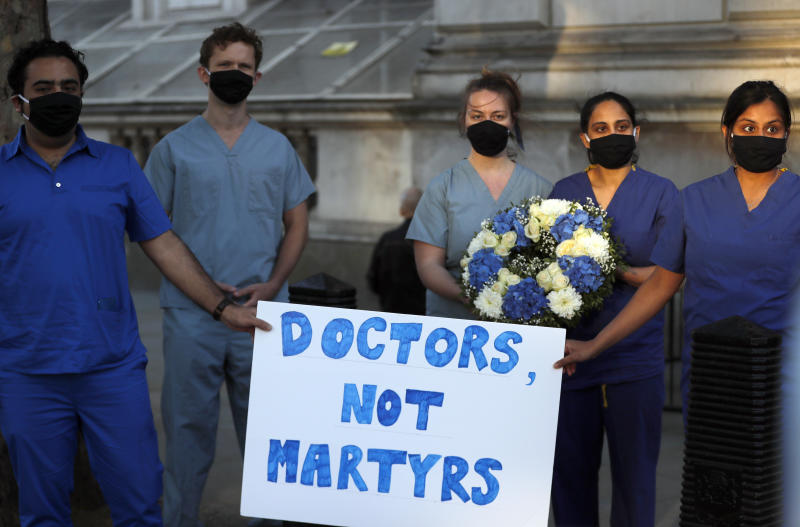 Doctors and nurses stand near Downing Street ahead of the clap to remember colleagues who have died fighting the coronavirus pandemic in London, Thursday, May 28, 2020. (AP Photo/Frank Augstein)