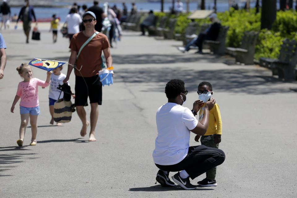 A man adjusts a child's mask before heading out to the sand at Orchard Beach in the Bronx borough of New York, Sunday, May 17, 2020. Parks, boardwalks and beaches attracted some crowds this weekend, though city beaches aren't officially open and won't be for the upcoming Memorial Day weekend. (AP Photo/Seth Wenig)