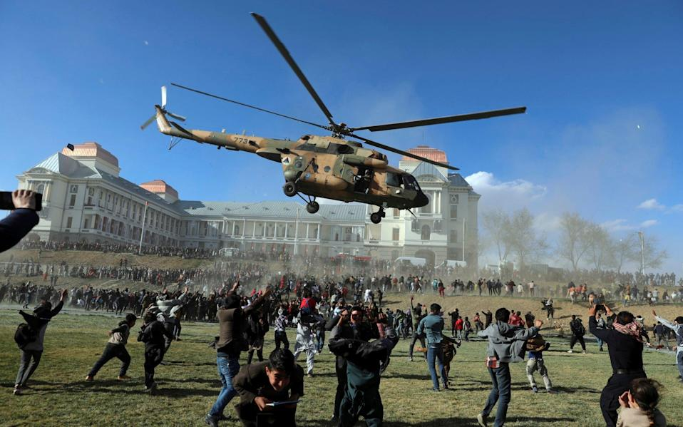 A military helicopter flies over people during the Afghan Security Forces Exhibition, at the Darul Aman Palace in Kabul, Afghanistan, Wednesday, March 3, 2021. The three-day military exhibition in Kabul allowed civilians to have a first hand view and take pictures of weaponry used by Afghan Security forces. (AP Photo/Rahmat Gul)