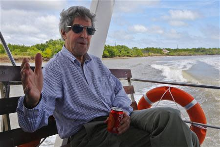 US Secretary of State John Kerry talks to reporters while riding a boat on the Mekong River Delta