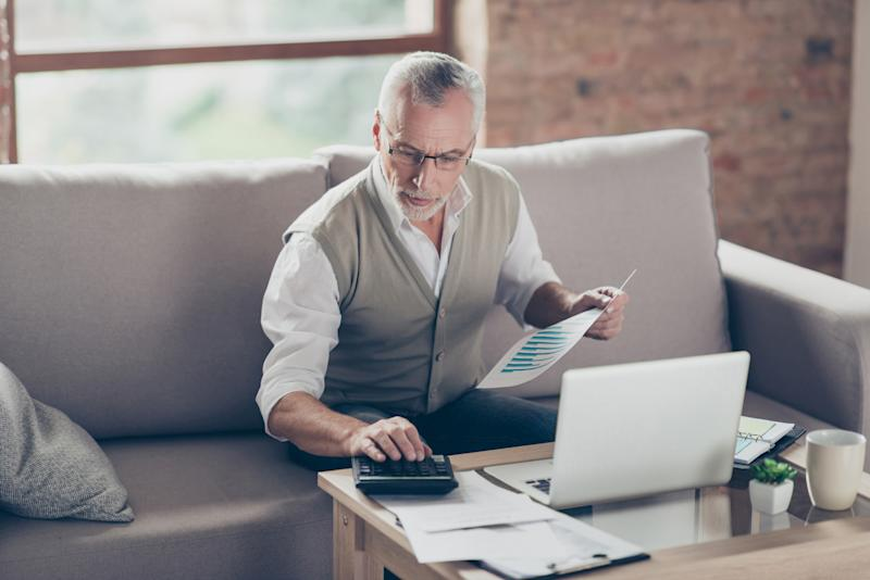 Older man sitting on couch holding document in one hand and typing on calculator with the other. Papers and a laptop are in front of him on a coffee table.