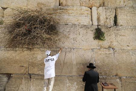 Western Wall Rabbi Shmuel Rabinowitz and a worker clear notes placed in the cracks of the Western Wall, Judaism's holiest prayer site, to create space for new notes ahead of the Jewish holiday of Passover, in Jerusalem's Old City, March 20, 2018. REUTERS/Ammar Awad