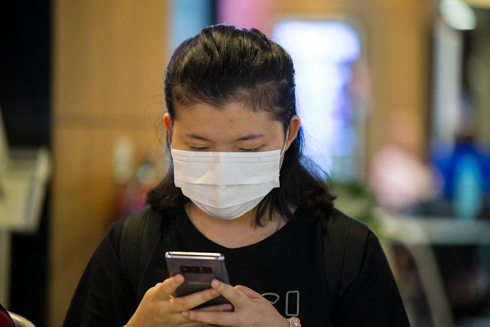 A woman wearing a face mask checks her phone. (PHOTO: Dhany Osman / Yahoo News Singapore)