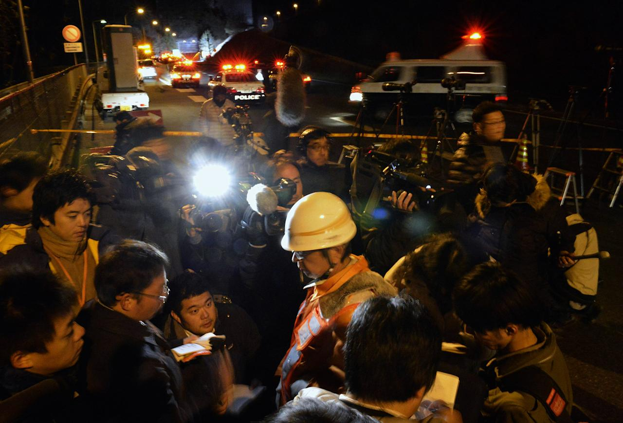 A worker of Central Nippon Expressway Co. speaks to the reporters near the Sasago Tunnel where a collapse took place in Koshu, Yamanashi Prefecture, central Japan, Sunday, Dec. 2, 2012. At least seven people were feared missing Sunday after about 150 concrete panels fell from the roof of the tunnel on the main highway linking Tokyo with central Japan. (AP Photo/Kyodo News) JAPAN OUT, MANDATORY CREDIT, NO LICENSING IN CHINA, FRANCE, HONG KONG, JAPAN AND SOUTH KOREA