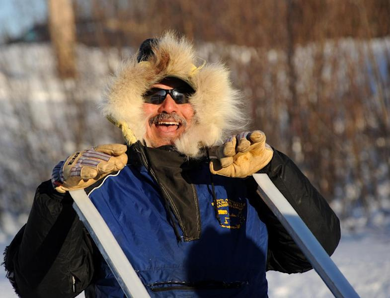 Gilbert Huntington, from Galena, Alaska, shares a laugh with Iditarod musher Hugh Neff, from Tok, at the Galena checkpoint during the 2014 Iditarod Trail Sled Dog Race on Friday, March 7, 2014. (AP Photo/The Anchorage Daily News Bob Hallinen)