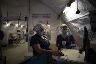 Nurses Karla Salazar, right, and Marisol Perez work in a tent set up to help treat COVID-19 patients at El Centro Regional Medical Center in El Centro, Calif., Tuesday, July 21, 2020. (AP Photo/Jae C. Hong)