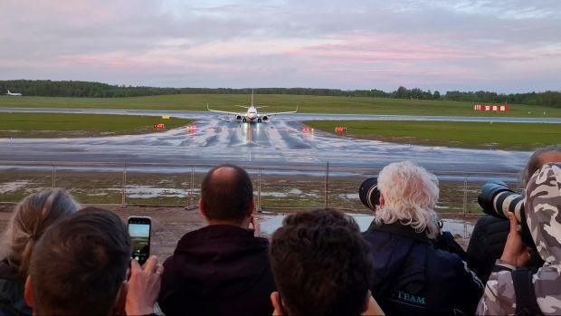 The hijacked Ryanair flight lands in Vilnius while onlookers snap photos.