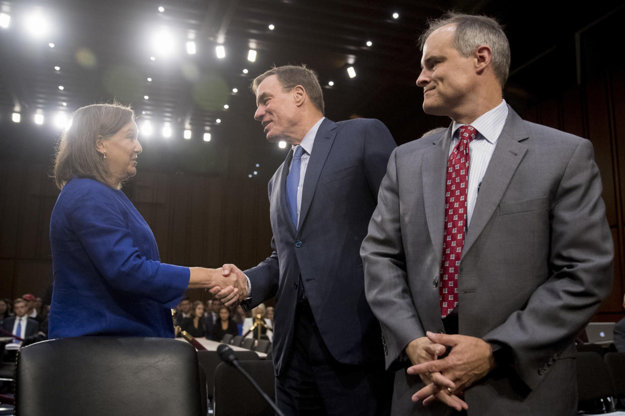 Former White House cybersecurity coordinator Michael Daniel, right, looks on as former Assistant Secretary of State Victoria Nuland, left, is greeted by committee vice chairman Mark Warner, D-Va. (Photo: Andrew Harnik/AP)