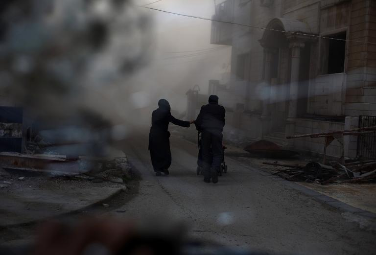 A picture taken from behind broken glass shows a couple pushing a pram as they rush to check their house following an air strike on the rebel-held Damascus suburb of Douma, on February 21, 2015