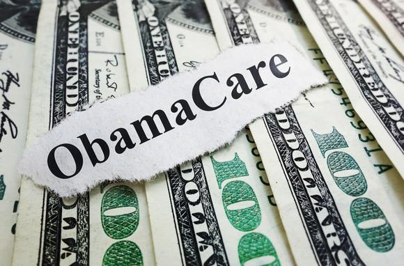 A piece of paper that reads Obamacare lying atop a fanned pile of hundred dollar bills.