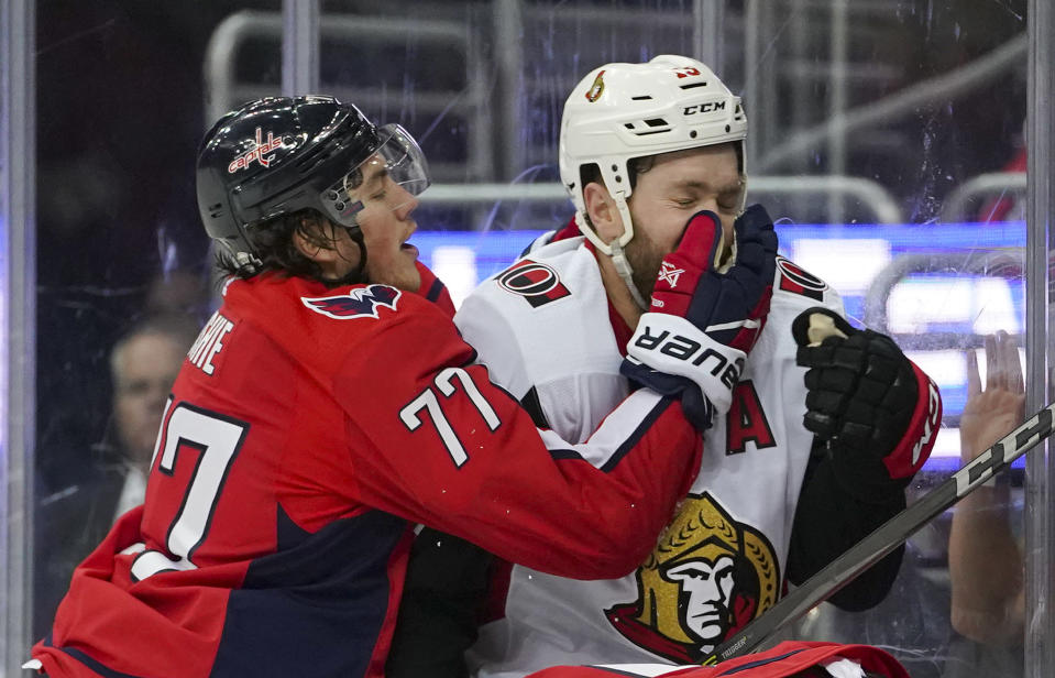 Washington Capitals right wing T.J. Oshie (77) and Ottawa Senators left wing Zack Smith (15) crash into the boards during the third period of an NHL hockey game Tuesday, Feb. 27, 2018, in Washington. The Capitals won 3-2. (AP Photo/Pablo Martinez Monsivais)