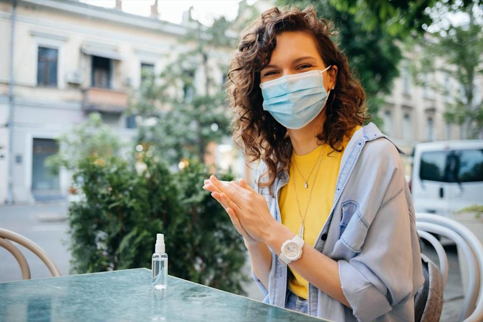 A happy young woman wearing a protective face mask disinfects her hands with an alcohol sanitizer, sitting at the table in the restaurant on a hot summer day.