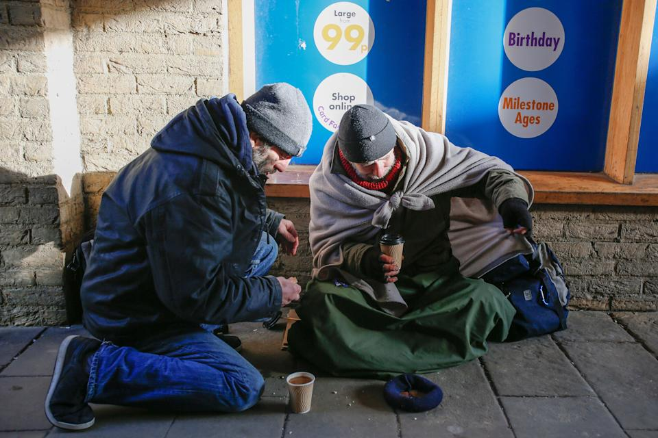 Two beggars in Ely with hot drinks given to them by the public (Picture: SWNS)