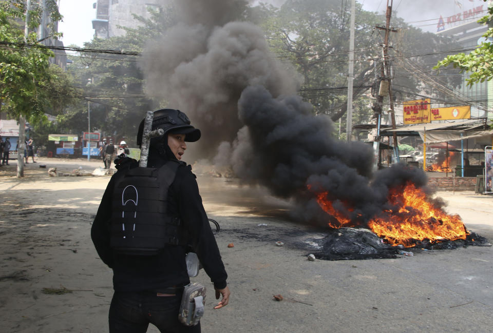FILE - In this March 27, 2021, file photo, an anti-coup protester stands near a fire during a demonstration in Yangon, Myanmar. One hundred days since their takeover, Myanmar's ruling generals maintain just the pretense of control over the country. There are fears the military takeover is turning Myanmar into a failed state. (AP Photo, File)