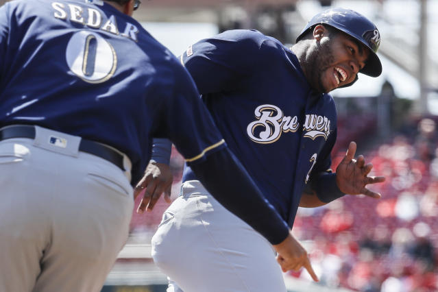 Milwaukee Brewers' Jesus Aguilar runs home to score on a single by Manny Pina off Cincinnati Reds starting pitcher Luis Castillo in the second inning of a baseball game, Wednesday, April 3, 2019, in Cincinnati. At left is Brewers third base coach Ed Sedar. (AP Photo/John Minchillo)