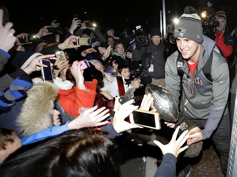 New England Patriots long snapper Joe Cardona (R) holds the Super Bowl trophy for fans following the teams arrival at Gillette Stadium, Monday, Feb. 6, 2017, in Foxborough, Mass, after defeating the Atlanta Falcons 34-28 Sunday in the NFL Super Bowl 51 football game in Houston. (AP Photo/Steven Senne)