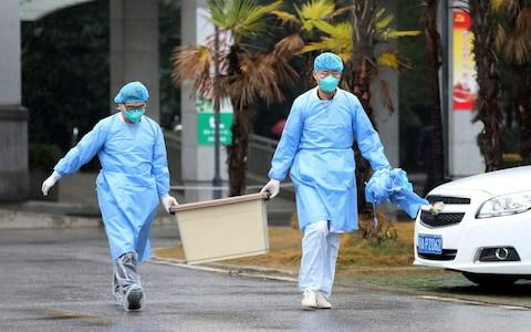 Medical staff wear protective gear after some colleagues were infected - Credit: Darley Shen/Reuters