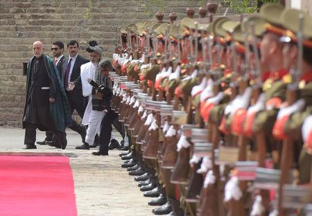 Former Afghan President Hamid Karzai (L) and Afghan President Ashraf Ghani (R) walk to attend a ceremony at the Presidential palace in Kabul, Afghanistan May 4, 2017.  REUTERS/Shah Marai/Pool