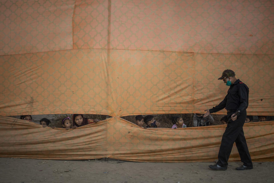 A private security man asks people not to look through from behind a curtain to watch Dussehra festival celebrations held where access was restricted due to the coronavirus pandemic in New Delhi, India, Sunday, Oct. 25, 2020. The Hindu festival season is traditionally laced with an unmatched fanfare and extravaganza, with socializing being the hallmark of the celebration. But this year's festivities have been scaled down. The celebrations, bereft of all the grandiose, have been muted. (AP Photo/Altaf Qadri)