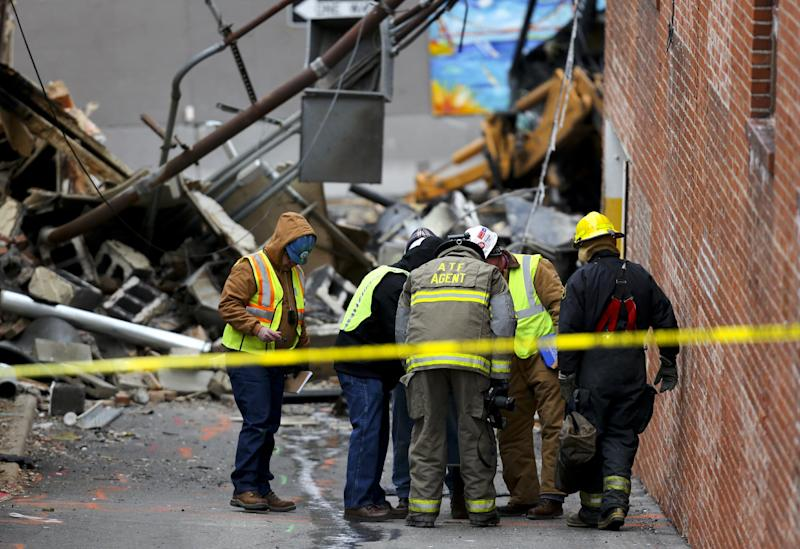 An ATF agent and other investigators look down a hole in an alley near JJ's restaurant after an explosion and fire tore through the establishment Tuesday evening near the Country Club Plaza Wednesday, Feb. 20, 2013, in Kansas City, Mo. The fire killed one person and injuring over a dozen. (AP Photo/Ed Zurga)