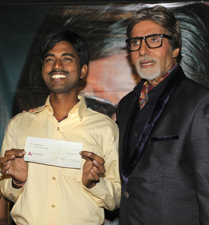 """In this Tuesday, Oct. 25, 2011, photograph, Sushil Kumar, left, with Bollywood actor Amitabh Bachchan, shows $1 million check after winning on an Indian game show, in Mumbai, India.  Kumar, a government clerk from a desolate region of eastern India, has become the first person ever to win $1 million on the popular Indian version of """"Who wants to be a Millionaire."""" (AP Photo)"""