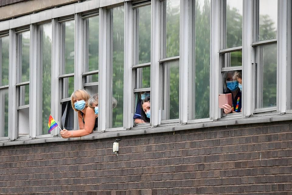 People wear masks as they watch the Prince of Wales and the Duchess of Cornwall meet other front line key workers who who have responded to the COVID-19 pandemic during a visit to Gloucestershire Royal Hospital.