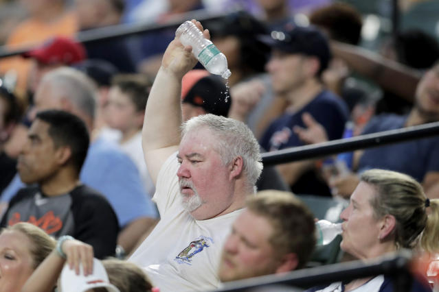 A spectator drops water on his head while watching the fourth inning of a baseball game between the Baltimore Orioles and the Boston Red Sox in hot weather, Saturday, July 20, 2019, in Baltimore. Temperatures reached the high 90s in Baltimore with the real feel over the triple digit mark. (AP Photo/Julio Cortez)