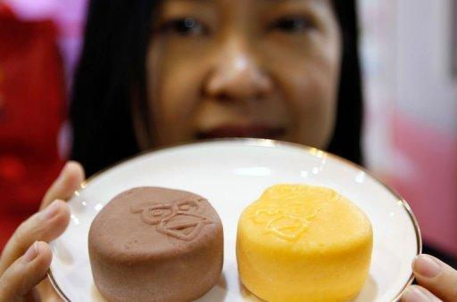 An employee displays the newly launched 'Angry Birds' mooncakes, a popular Chinese baked pastry made from lotus seed paste and salted egg yolks available this time of the year, during the Hong Kong Food Expo on August 14. The pastries are named after the popular mobile game