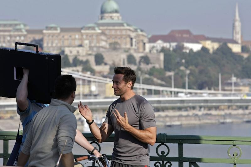 Australian actor Hugh Jackman chats with crew members on the Szabadsag bridge in Budapest during a film shoot, in 2011 (AFP Photo/Ferenc Isza)