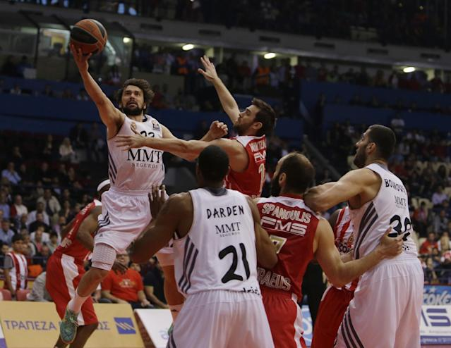 Olympiakos' Vangelis Mantzaris, right, jumps to stop Real Madrid's Sergio Llull during a Euroleague playoff game 3 basketball match at the Peace and Friendship Arena in Athens' port of Piraeus on Monday, April 21, 2014. (AP Photo/Thanassis Stavrakis)
