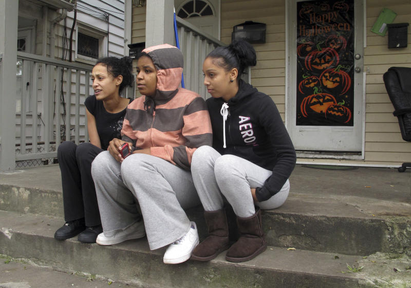 In this Thursday, Nov. 1, 2012 photo, roommates Yvonne Figueroa, left, Jess Santiago, center, and Francheska Suarez huddle on their front porch talking to a friend on the sidewalk in Bridgeport, Conn. They were without power since Superstorm Sandy hit Monday, and have been heating their home with their gas stove. Santiago said she had struggled to keep her 1-year-old son warm. (AP Photo/Dave Collins)