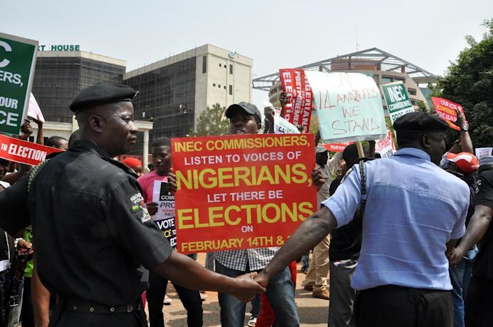 Police officers holds hands to block people holding sign protesting as chairman of the Independent National Electoral Commission announced that Nigeria has postponed its presidential election (AFP Photo/)