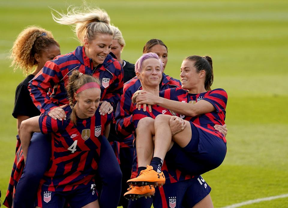 USA forward Megan Rapinoe holds up defender Kelley O'Hara with other teammates after defeating Mexico at Pratt & Whitney Stadium. David Butler II-USA TODAY Sports
