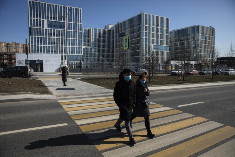A couple wearing face masks cross the street in front of the hospital for coronavirus patients in Kommunarka settlement, outside Moscow, Russia, Tuesday, March 24, 2020, with Russia only reporting a few hundred virus cases. The highly contagious COVID-19 coronavirus can cause mild symptoms, but for some it can cause severe illness including pneumonia. (AP Photo/Pavel Golovkin)