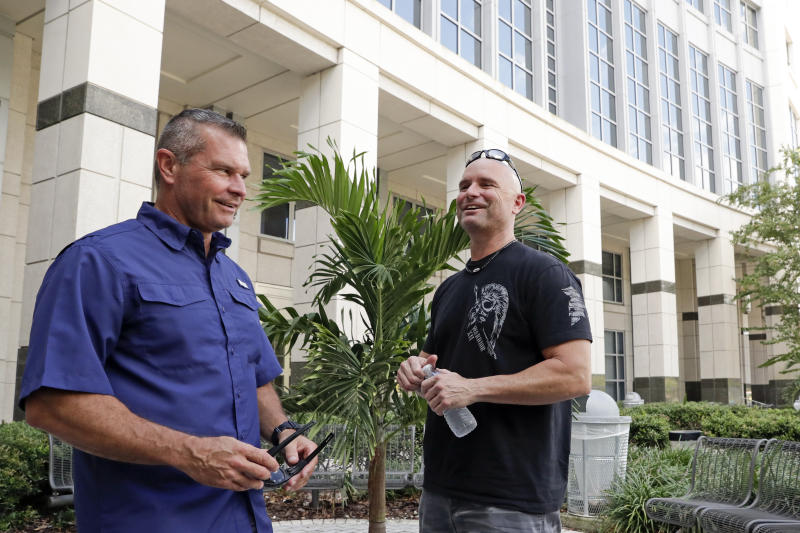 In this Thursday, Sept. 12, 2019, photo, Dave Stull, left, and Eric Reynolds, both police officers, get together in Orlando, Fla. They recently found out they were half brothers though a DNA test. (AP Photo/John Raoux)