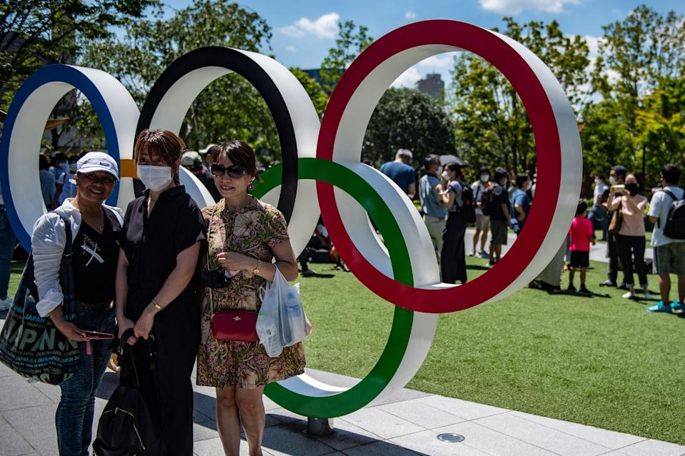 People pose in front of the Olympic Rings near the Olympic Stadium in Tokyo ahead of this Friday's opening ceremony