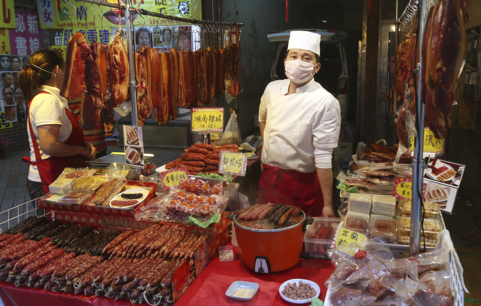 A vendor wears a face masks to help curb the spread of the coronavirus at his shop at a market in Taipei, Taiwan, Monday, Jan. 25, 2021. (AP Photo/Chiang Ying-ying)