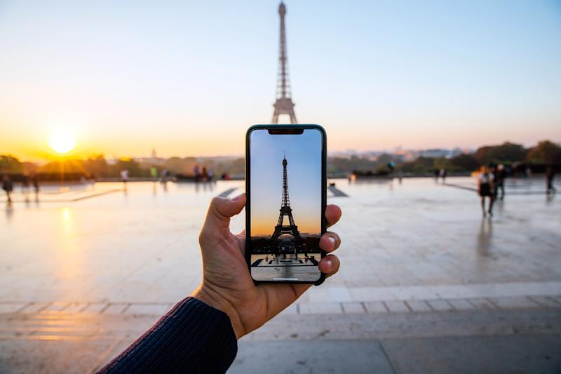 Tourist taking picture of Eiffel Tower with smart phone, personal perspective view, Paris, France